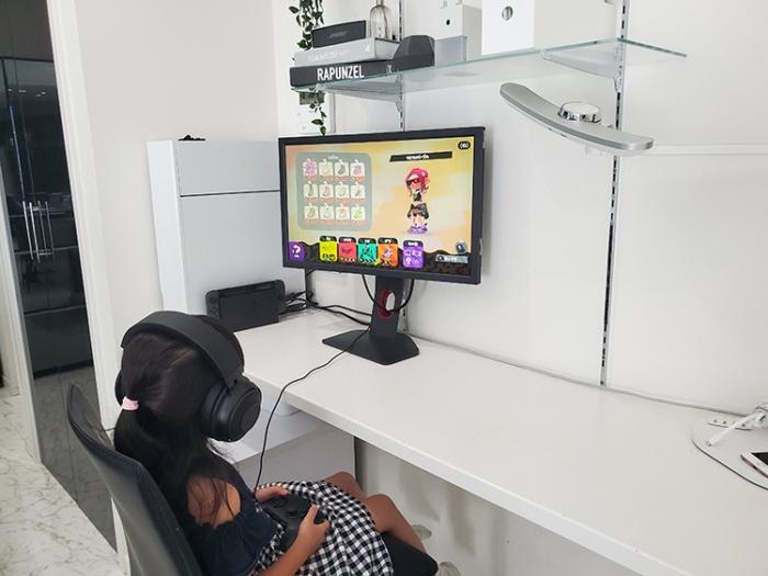リビングの一角のゲームスペースでゲームをする子供。